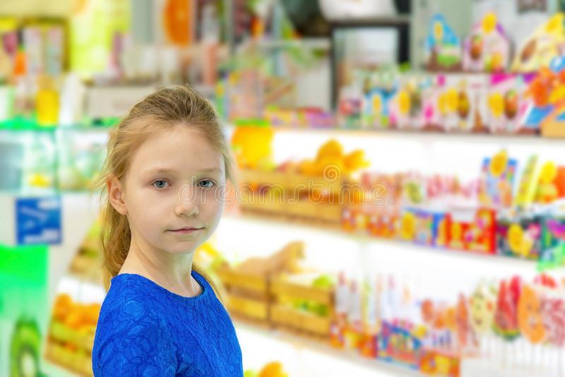 Une belle et mignonne fille se tient à la fenêtre de magasin et regarde dans la caméra, près des sucreries douces et savoureuses photos libres de droits