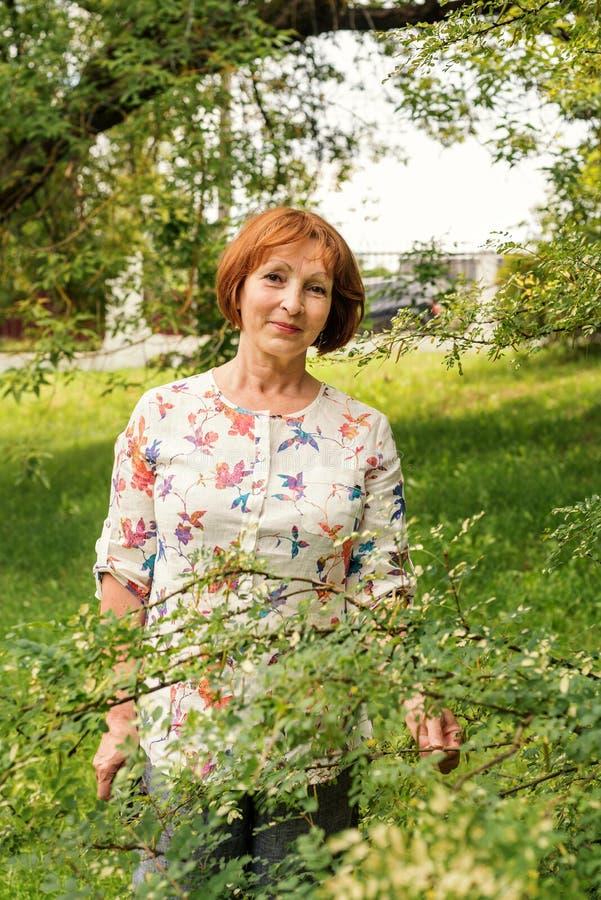 Une belle femme agée dans des vêtements flaxen se tient tranquilly dans son jardin vert images stock