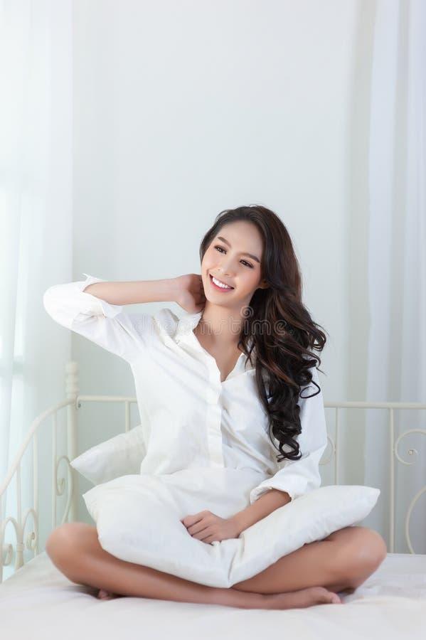 Une belle femme asiatique dans une chemise blanche qui s'étend et sourit heureusement sur un lit blanc photographie stock libre de droits