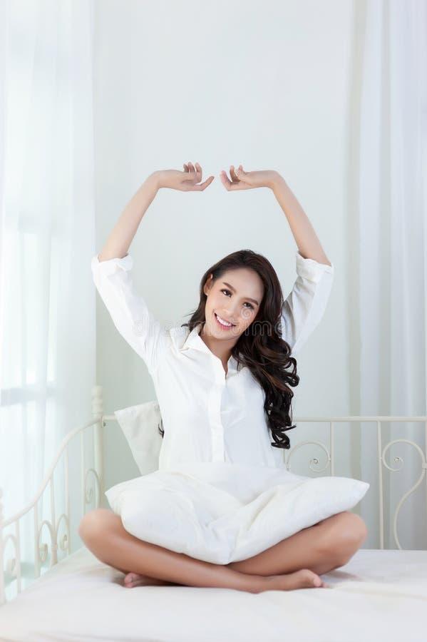 Une belle femme asiatique dans une chemise blanche qui s'étend et sourit heureusement sur un lit blanc photos stock
