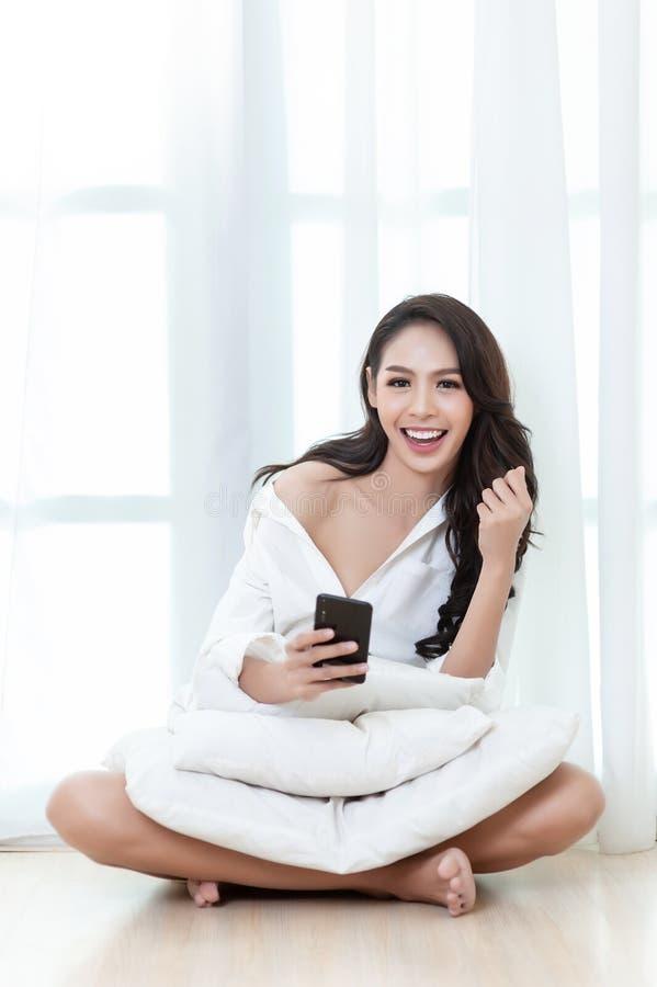 Une belle femme asiatique dans un smartphone blanc sexy de shirtwhith dans sa main souriant heureusement sur un plancher dans la  image stock