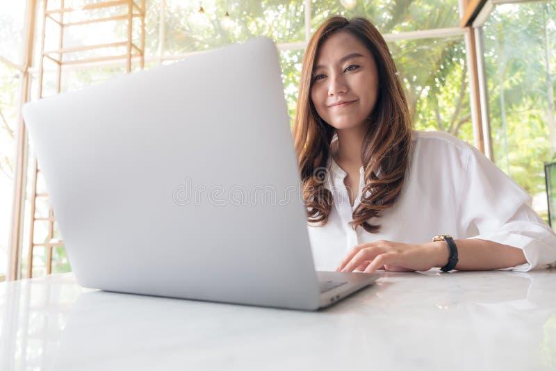 Une belle femme asiatique employant et introduisant au clavier sur l'ordinateur portable le café photo libre de droits