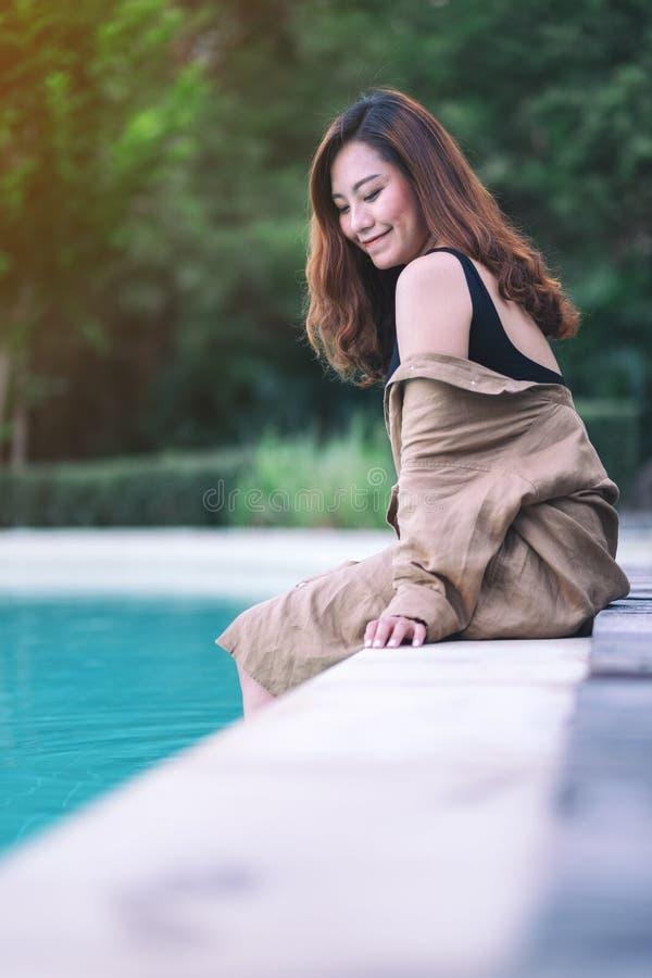 Une belle femme asiatique a eu plaisir ? s'asseoir par la piscine photographie stock