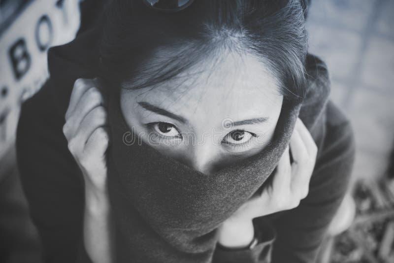 Une belle femme asiatique regardant et fermant sa bouche avec le tissu photos stock