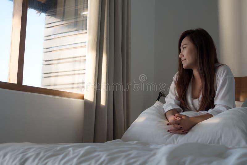 Une belle femme asiatique s'asseyant sur le lit et regardant en dehors de la fenêtre photographie stock