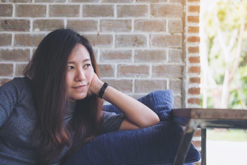 Une belle femme asiatique s'asseyent avec le menton se reposant sur ses mains au-dessus d'un oreiller bleu avec se sentir heureus photographie stock