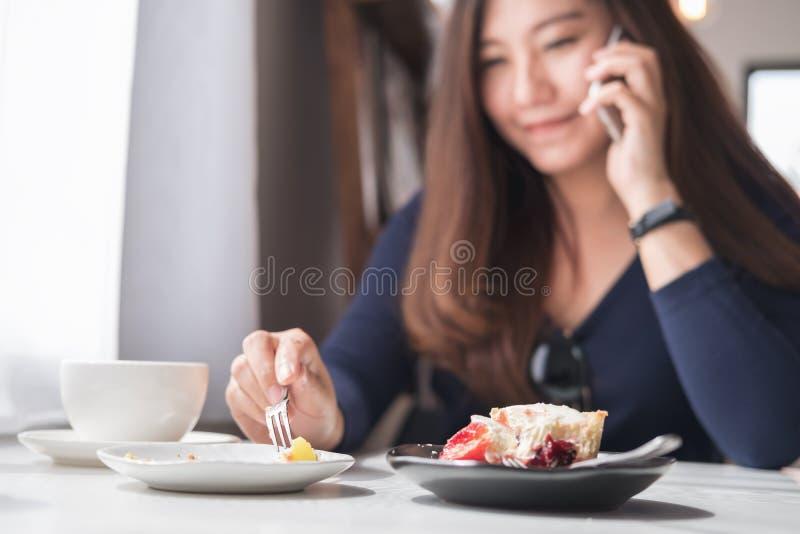 Une belle femme asiatique souriante se tenant et parlant au téléphone intelligent avec la tasse de café blanc et les plats de des photos stock