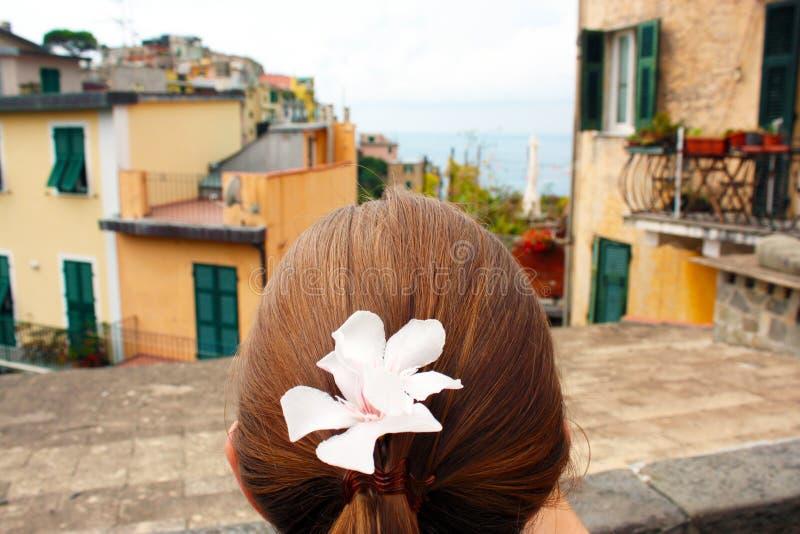 Une belle femme avec une fleur rose dans ses cheveux regardant au-dessus de la belle ville de Corniglia dans Cinqueterre, Italie image stock