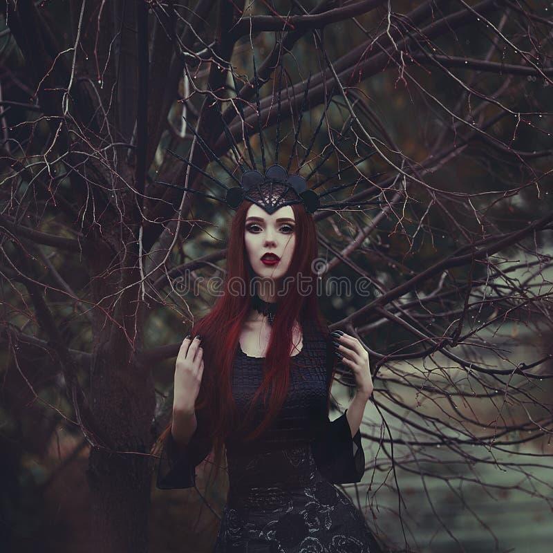 Une belle femme avec la peau pâle et les longs cheveux rouges dans une robe noire et dans le crownk noir Sorcière de fille avec l photos libres de droits