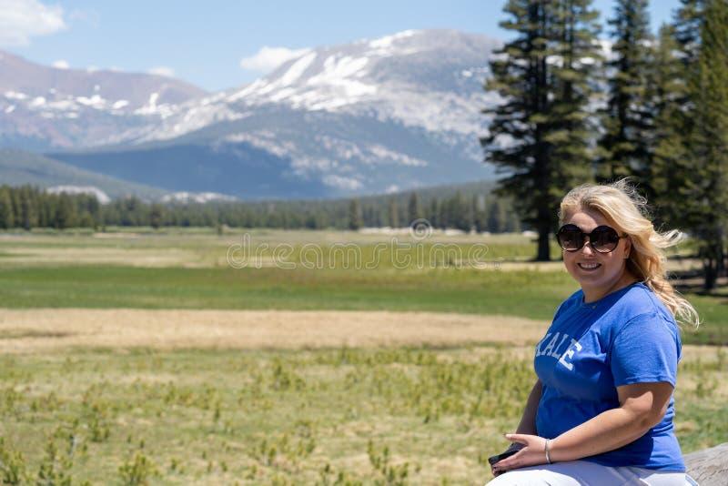 Une belle femme blonde pose dans les prairies de Tuolumne dans le parc national de Yosemite, portant des lunettes de soleil photos stock