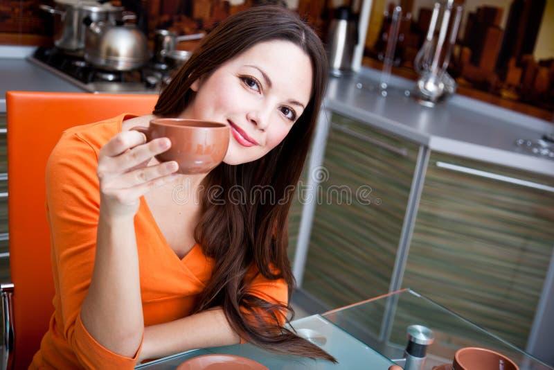 Une belle femme boit dans la cuisine photo libre de droits