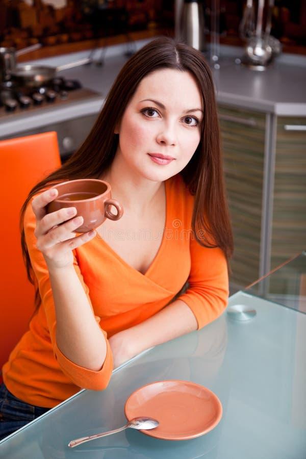 Une belle femme boit dans la cuisine image libre de droits