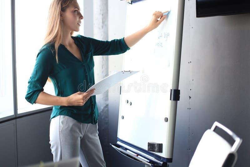 Une belle femme d'affaires se tient près d'un tableau à feuilles mobiles et y examine l'information images libres de droits