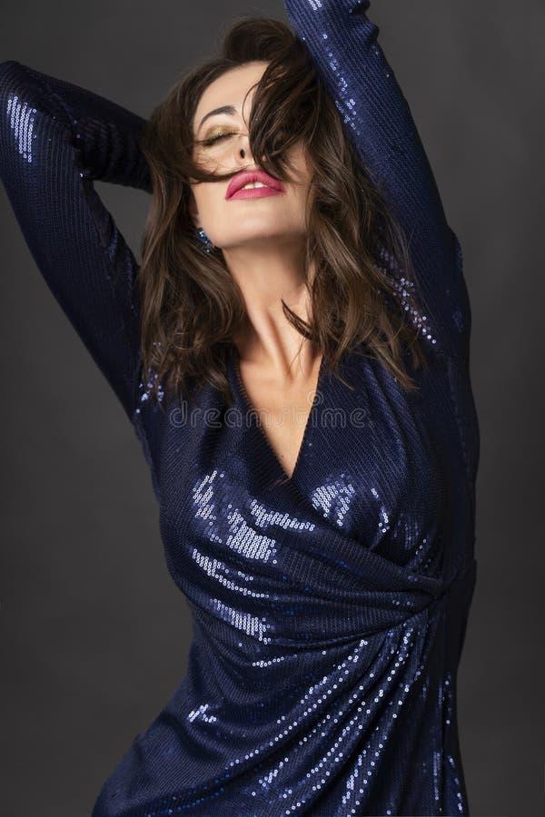 Une belle femme de brune portant une robe bleue scintillante sur un fond gris sensuel touche ses cheveux et les fait face avec el image stock