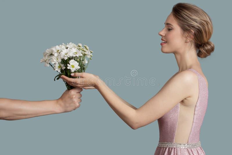 Une belle femme donne des fleurs de camomille photographie stock