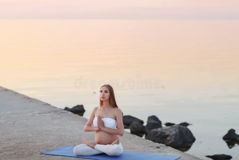 Une belle femme enceinte faisant le yoga sur le côté de mer images stock