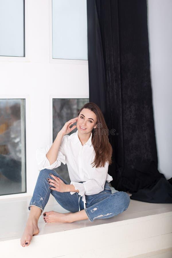 Une belle femme joyeux de sourire avec les cheveux foncés, habillés dans des vêtements sport dans les jeans et une chemise, regar image libre de droits