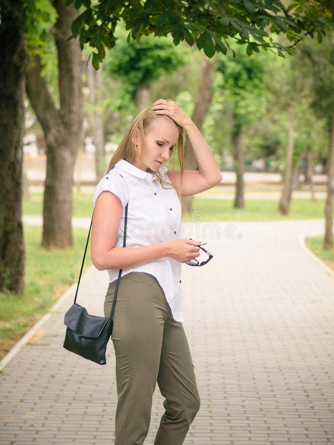 Une belle femme redresse ses cheveux avec sa main en parc de ville photographie stock libre de droits