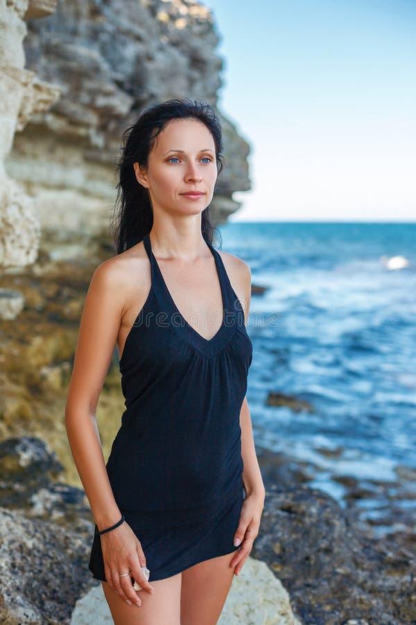 Une belle femme se tient sur la plage et regarde la mer image stock