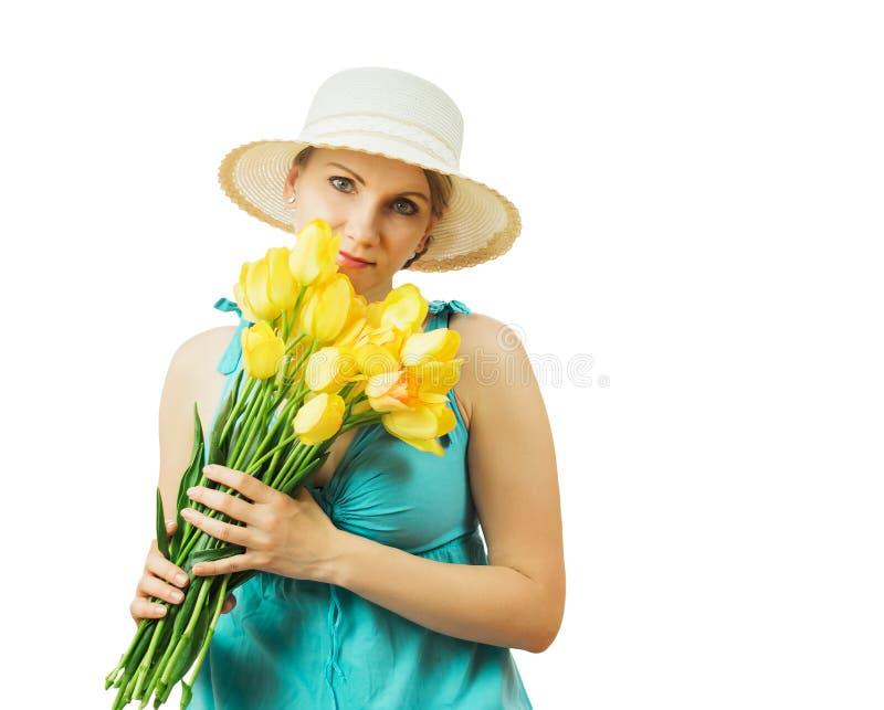 Une belle femme tient dans des ses mains beaucoup de tulipes jaunes images stock