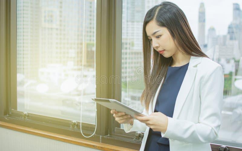 Une belle femme utilise le comprimé près de la fenêtre images stock