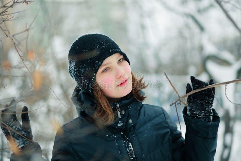Une belle fille a écarté les branches d'un arbre photo libre de droits