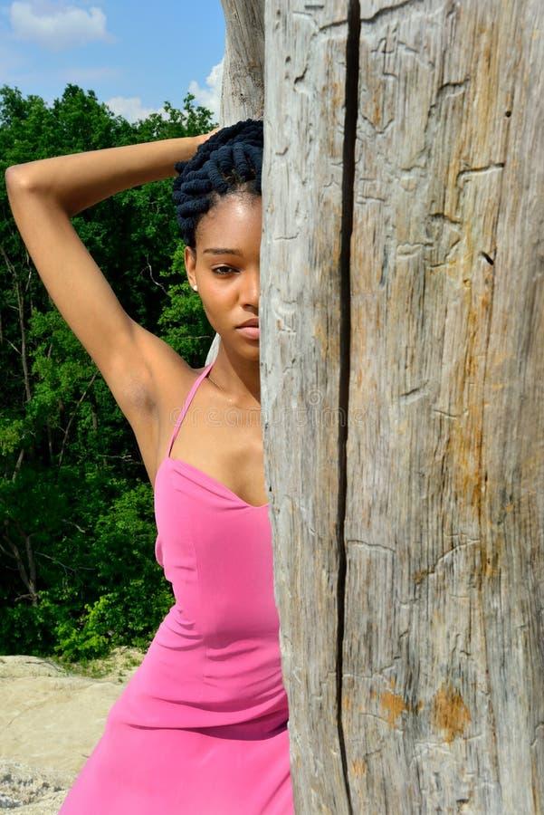 Une belle fille afro-américaine, avec redoute sur sa tête, se tient sur une haute colline moitié-cachant son visage derrière photo libre de droits