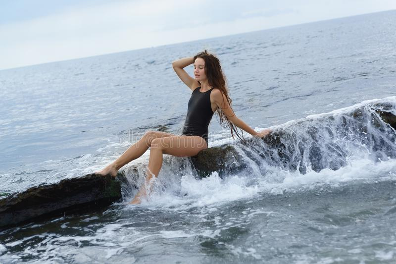 Une belle fille aux cheveux longs mince dans un maillot de bain noir s'assied sur une pierre sur la mer un jour nuageux d'été images stock