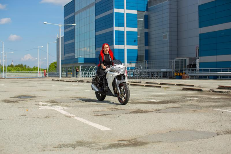 Une belle fille aux tresses rouges conduit une moto blanche photos stock
