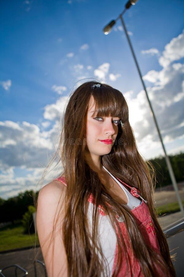 Une belle fille avec le long cheveu regardant l'appareil-photo images stock