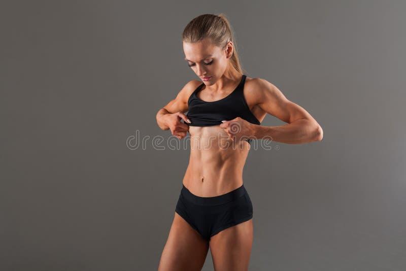 Une belle fille avec un corps maigre et musculaire fin soulève un gilet pour montrer de beaux muscles abdominaux photographie stock