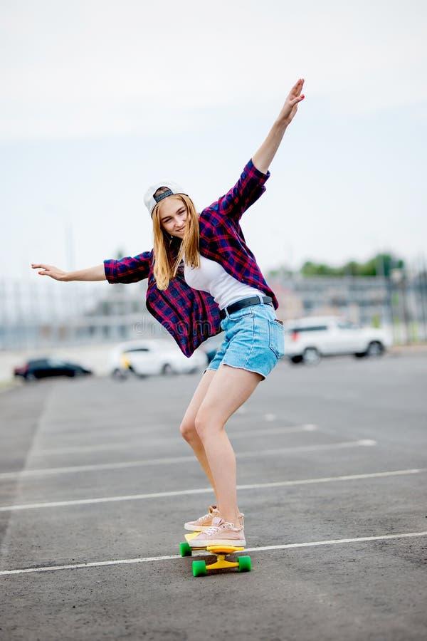 Une belle fille blonde portant les caleçons à carreaux de chemise, de chapeau et de denim longboarding tout en étirant ses mains photos libres de droits