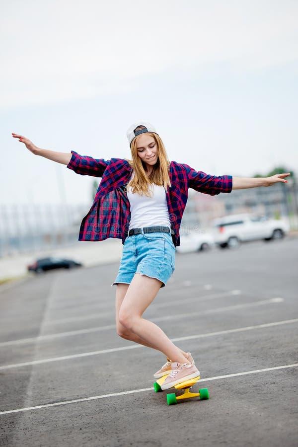 Une belle fille blonde portant les caleçons à carreaux de chemise, de chapeau et de denim longboarding tout en étirant ses mains photo libre de droits