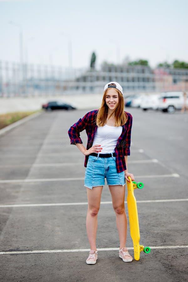 Une belle fille blonde portant les caleçons à carreaux de chemise, de chapeau et de denim se tient sur le parking avec un longboa photographie stock libre de droits