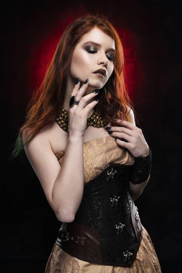 Une belle fille cosplay rousse réfléchie utilisant une robe et un corset de style victorien de steampunk Portrait Noir et rouge photo stock