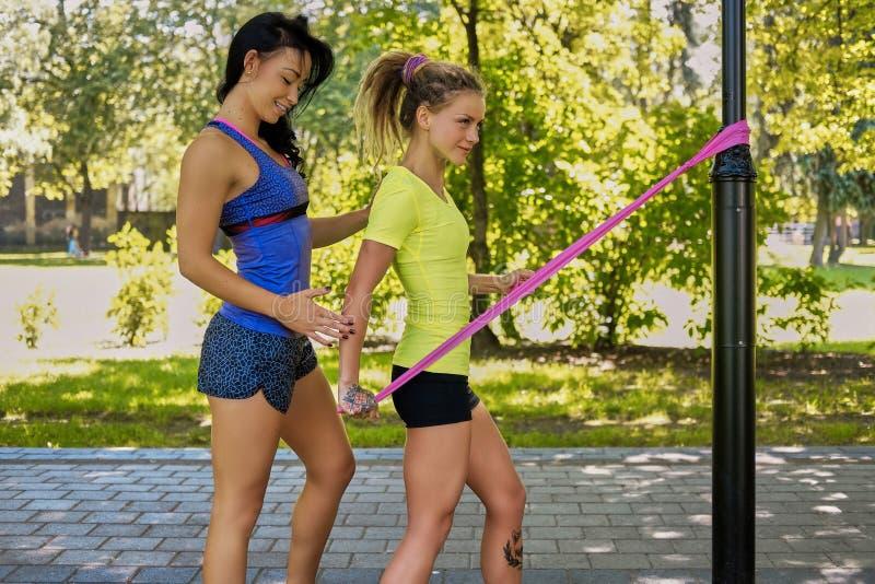 Une belle fille de forme physique avec son entraîneur, séance d'entraînement avec la suspension, se tenant près d'un courrier de  photo libre de droits