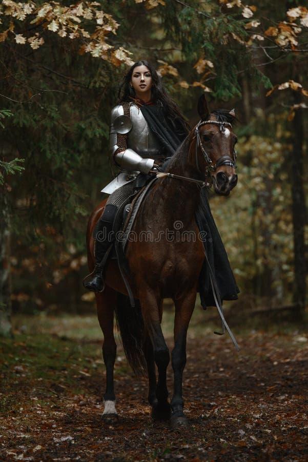 Une belle fille de guerrier avec un chainmail et une armure de port d'épée montant un cheval dans une forêt mystérieuse images libres de droits