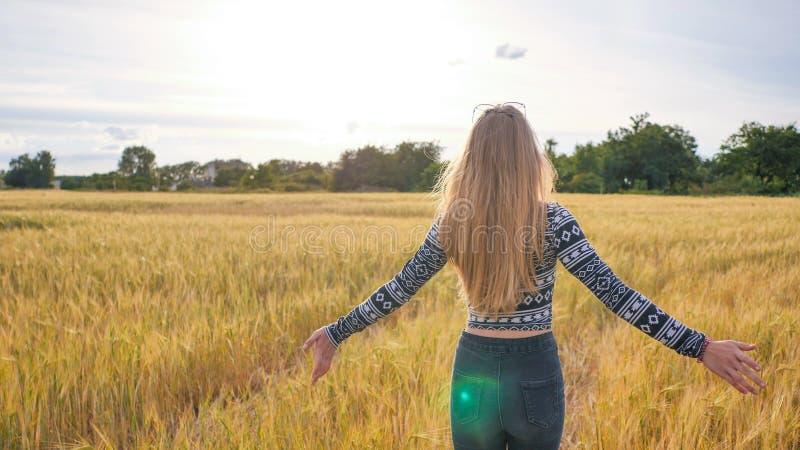 Une belle fille de l'adolescence blonde court à travers un champ de blé et tourne autour et sourit images libres de droits