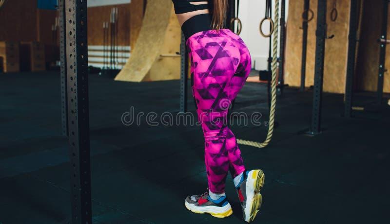 Une belle fille de sports forme un biceps avec une tige dans des ses mains dans le gymnase image libre de droits