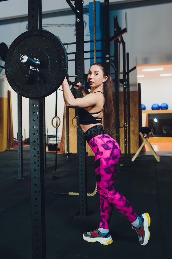 Une belle fille de sports forme un biceps avec une tige dans des ses mains dans le gymnase photo libre de droits