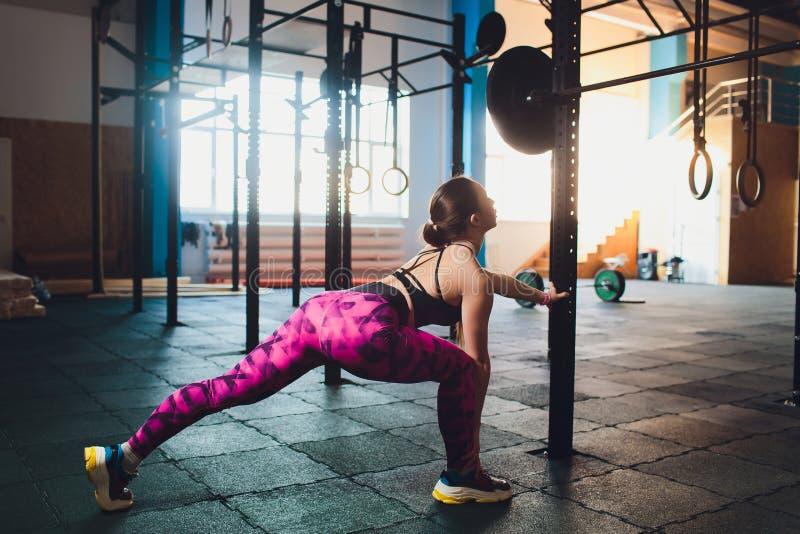 Une belle fille de sports forme un biceps avec une tige dans des ses mains dans le gymnase images libres de droits