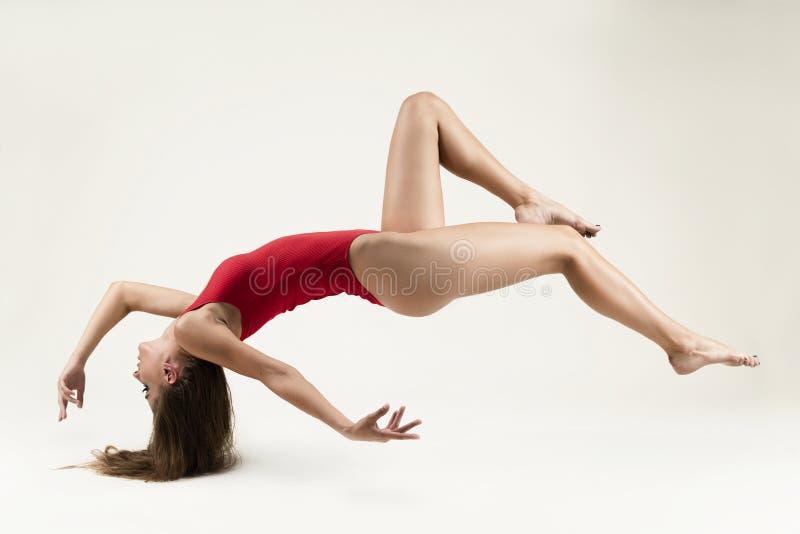 Une belle fille mince aux jambes longues aux cheveux longs portant un corps rouge fait de la lévitation sur un fond blanc, toucha image stock