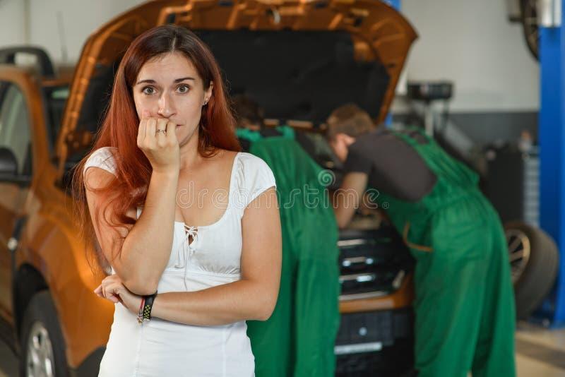 Une belle fille pose pour une photo tandis que, deux jeunes mécaniques dedans photos libres de droits