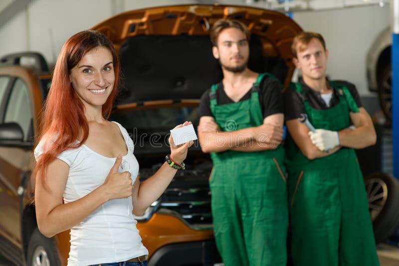 Une belle fille pose pour une photo tandis que, deux jeunes mécaniques dedans photo stock