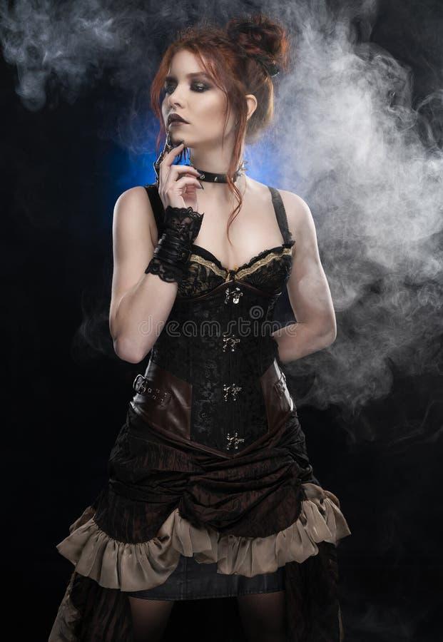 Une belle fille rousse de cosplayer utilisant un costume de style victorien de steampunk avec un grand sein dans une position pro images libres de droits