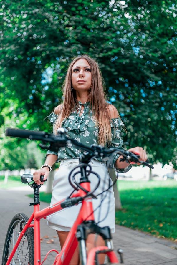 Une belle fille se tient à côté d'une bicyclette rouge sur un fond des arbres en parc En ?t? sur l'air frais lifestyle photos stock