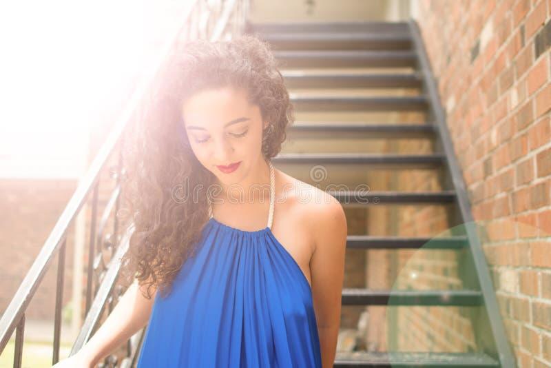 Une belle jeune femme avec les cheveux bouclés bruns foncés descend un vol des escaliers photo stock