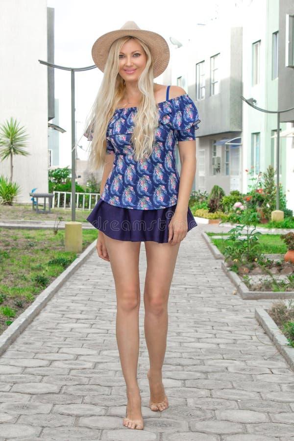 Une belle jeune femme blonde avec de longues jambes minces dans une jupe courte et un chapeau se tient posante dehors photo stock