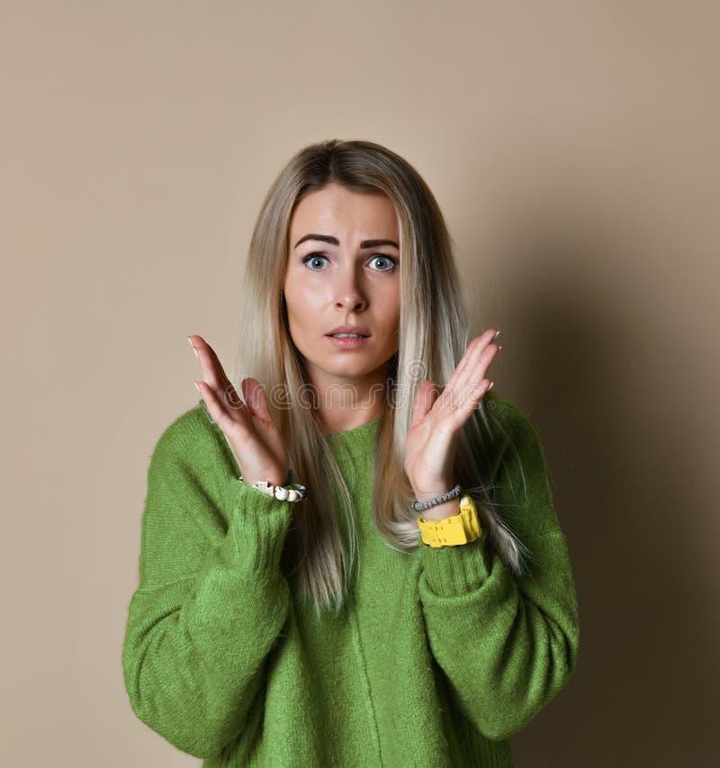 Une belle jeune femme blonde est étonnée et juge des mains avec son visage ouvertes sa bouche photographie stock libre de droits