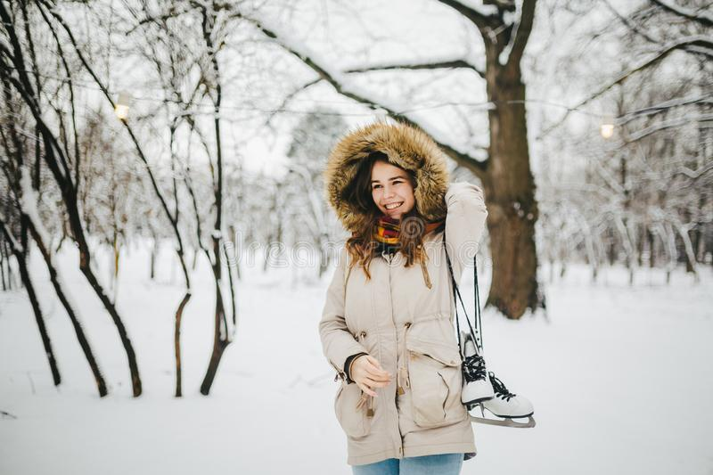 Une belle jeune femme caucasienne se tient en parc neigeux dans une veste avec un capot et une fourrure sur sa tête dans des jean images libres de droits